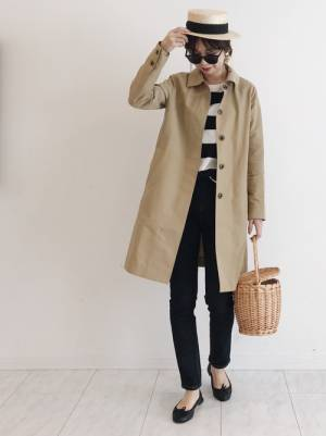 ボーダートップス、デニムパンツにベージュのステンカラーコートを着た女性