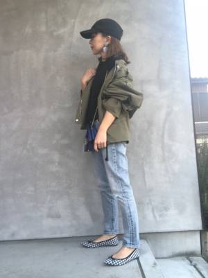 黒のトップス、デニムパンツにカーキのミリタリージャケットを着た女性