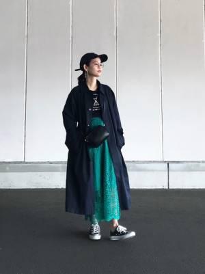 黒のロゴT、グリーンのレーススカートにネイビーのステンカラーコートを着た女性