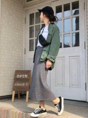 白のロゴT、グレーのニットスカートにカーキのミリタリージャケットを着た女性