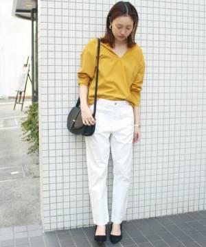 イエローシャツに白パンツを履いた女性