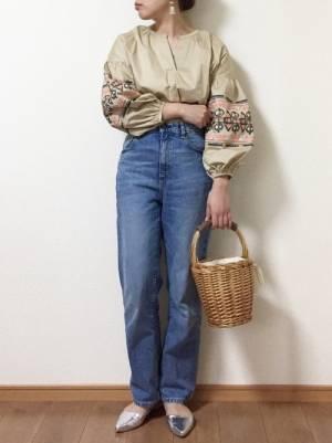 ベージュの刺繍ブラウスにデニムパンツを履いた女性