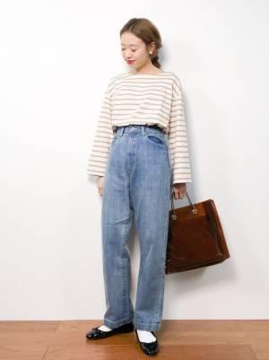 ベージュのボーダートップスにデニムパンツを履いた女性