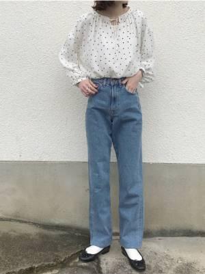 白のドット柄ブラウスにデニムパンツを履いた女性