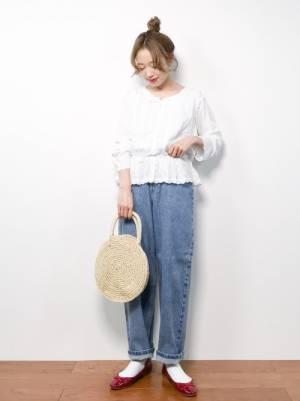 白の刺繍ブラウスにデニムパンツを履いた女性