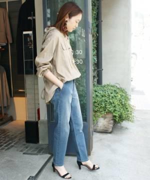 ベージュのパーカーにデニムパンツを履いた女性