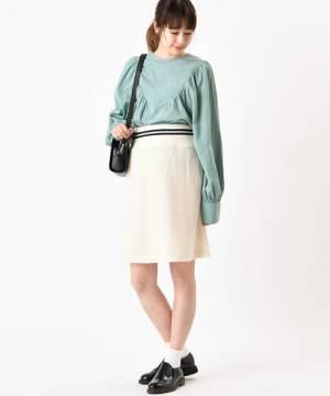 ライトブルーのブラウスに白のリブスカートを履いた女性
