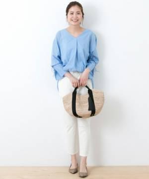ライトブルーのブラウスに白のパンツを履いた女性