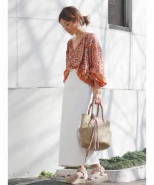 オレンジの花柄ブラウスに白のタイトロングスカートを履いた女性