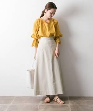 黄色のブラウスに白のロングスカートを履いた女性