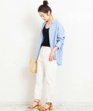 黒のトップス、白のパンツにブルーのストライプシャツを履いた女性