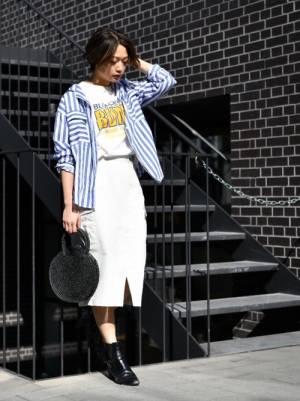白のロゴT、白のタイトスカートにブルーのストライプシャツを羽織った女性