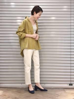 白のトップス、白のパンツに黄色のストライプシャツを着た女性