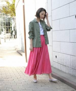 白のトップスにピンクのスカートを合わせて、ミリタリーシャツを羽織った女性