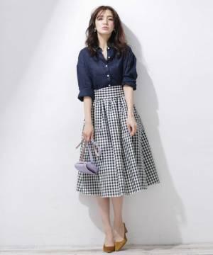 ダークネイビーのリネンシャツにギンガムチェックのスカートを合わせた女性