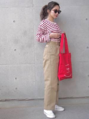 赤のボーダートップスにチノパン、赤のトートバッグを持った女性