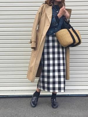黒のトップスにデニムジャケットを重ねてチェックのスカートを合わせ、トレンチコートを羽織った女性