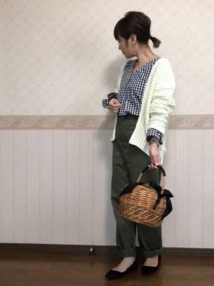 ギンガムチェックのブラウスにカーキのパンツを合わせて、白のカーディガンを羽織った女性
