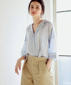 ストライプ開襟シャツにベージュパンツを履いた女性