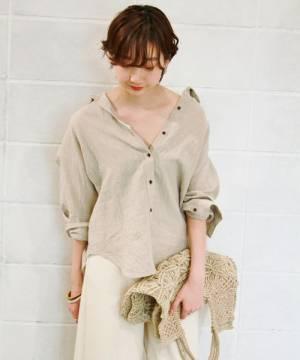 ベージュのリネンシャツに雑材クラッチのコーデ