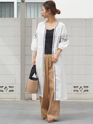 黒のトップス、ベージュのチノパンに白の刺繍ガウンを着た女性