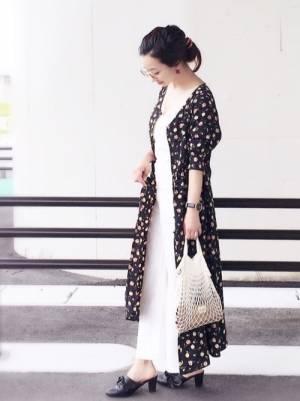 白のワンピースに黒の花柄ガウンを着た女性