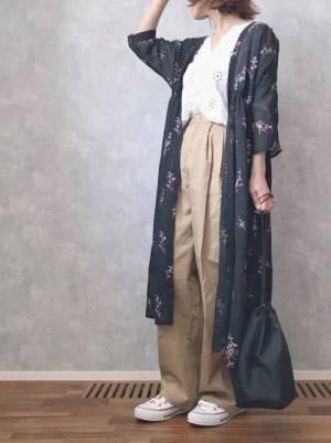 白の刺繍ブラウス、ベージュのチノパンに黒の花柄ガウンを着た女性