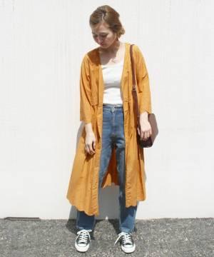白のトップス、デニムパンツにオレンジのガウンを着た女性