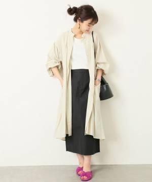 白のトップス、黒のスカートにベージュのガウンを着た女性