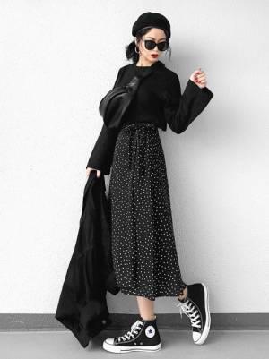 黒のTシャツにGUのドット柄フレアスカートを合わせた女性