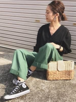 黒のVネックブラウスにグリーンのハイウエストチノワイドパンツを合わせた女性