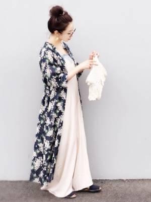 淡い色のサテンのサロペットにネイビーの花柄の前開きワンピースを羽織った女性