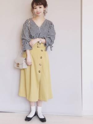 ギンガムチェックのブラウスに黄色のフレアスカートを履いた女性