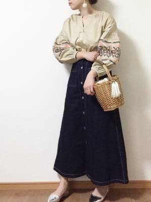 ベージュの刺繍ブラウスにデニムフレアスカートを履いた女性