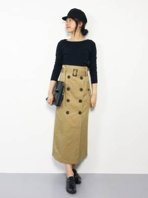 黒のトップスにベージュのタイトスカートを履いた女性