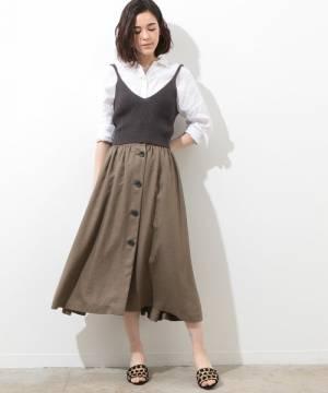 白のシャツ、グレーのニットキャミにカーキのフレアスカートを履いた女性
