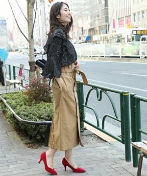 黒のドット柄ブラウスにベージュのタイトスカートを履いた女性