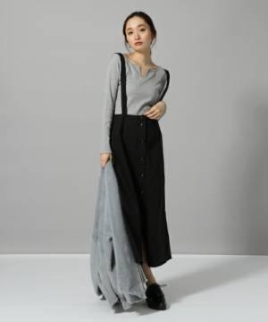 グレーのトップスに黒のサロペスカートを履いた女性