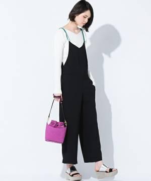 白のリブトップスに黒のサロペットを着た女性