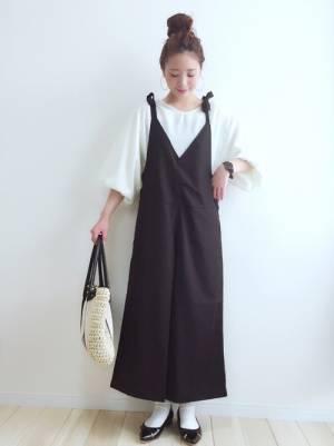 白のトップスに黒のサロペットを着た女性