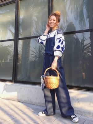 刺繍ブラウスにデニムサロペットを着た女性