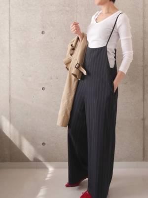 白のトップスに黒のストライプ柄サロペットを着た女性