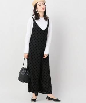 白のトップスに黒のドット柄サロペットを着た女性