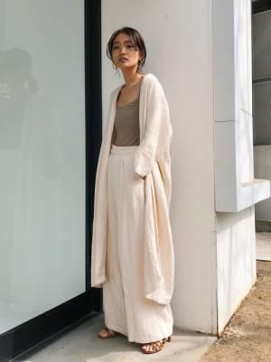 ベージュのトップス、白のワイドパンツに白のリネンガウンを着た女性
