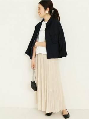 白T、白のプリーツスカートに黒のジャケットを着た女性