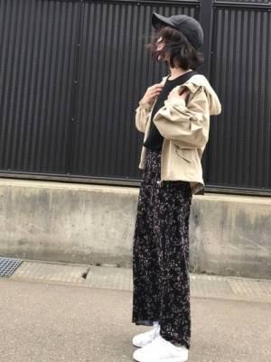 黒のトップス、黒の花柄パンツにベージュのパーカーを着た女性