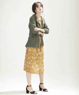 オレンジの花柄ワンピースにジャケットを着た女性