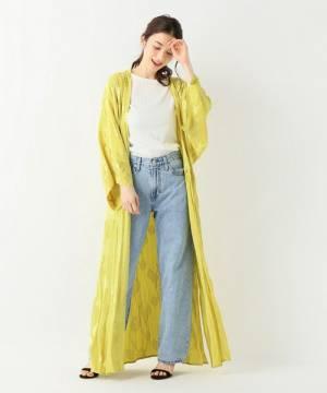 白のトップス、デニムパンツに黄色のロングガウンを着た女性